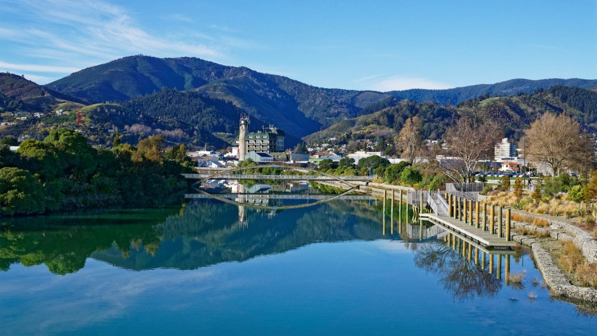 NZ Nelson Panorama of Nelson City reflected in the still waters of the Maitai River