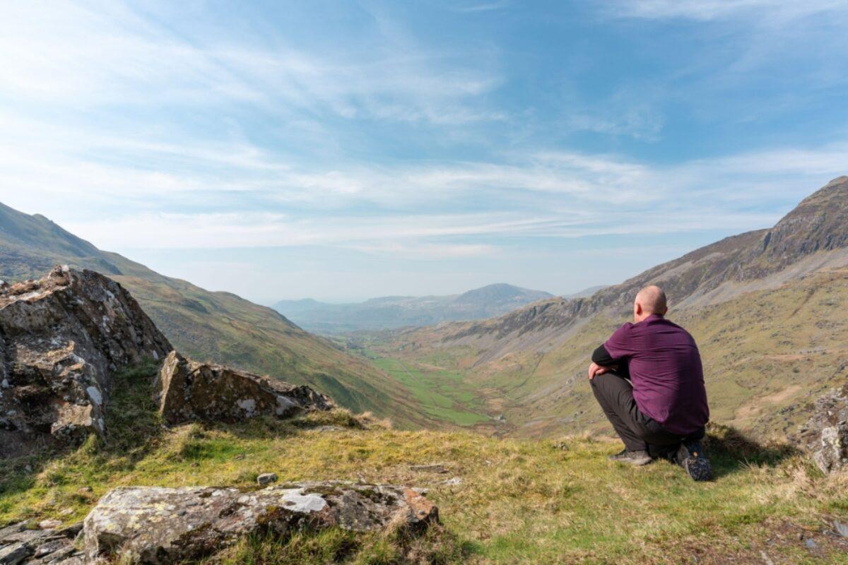 Snowdonia Way walker admiring the view of Cwm Croesor from Cnicht Gwynedd Wales uk